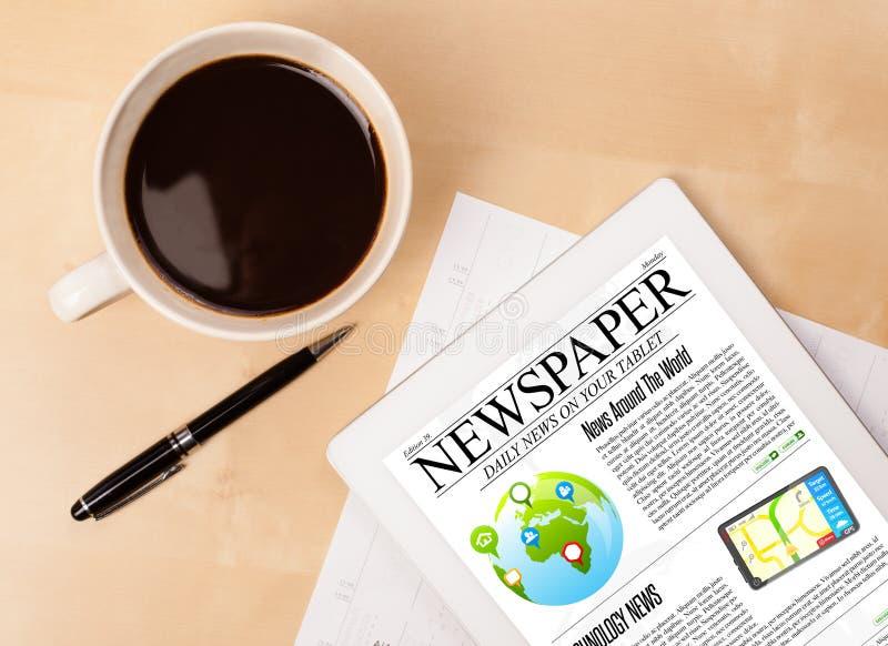 Il pc della compressa mostra le notizie sullo schermo con una tazza di caffè su uno scrittorio fotografia stock libera da diritti