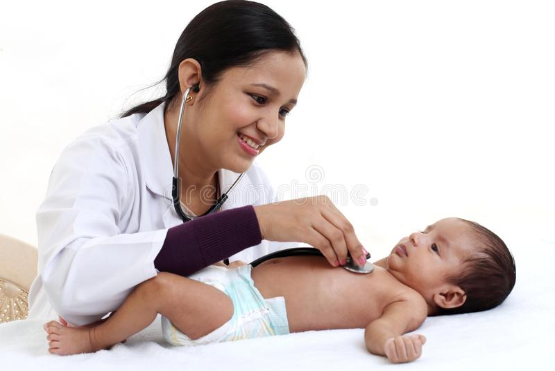 Il pediatra femminile allegro tiene il neonato fotografia stock libera da diritti