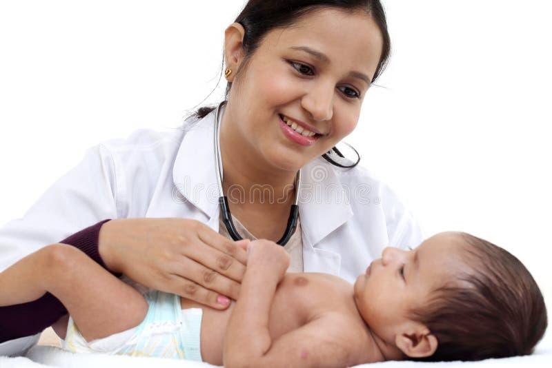 Il pediatra femminile esamina il neonato fotografie stock