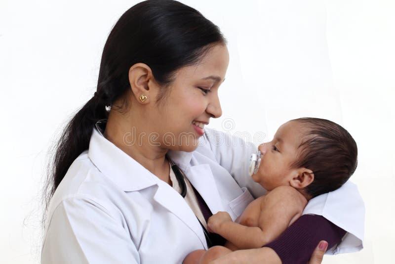 Il pediatra femminile tiene il neonato immagini stock libere da diritti