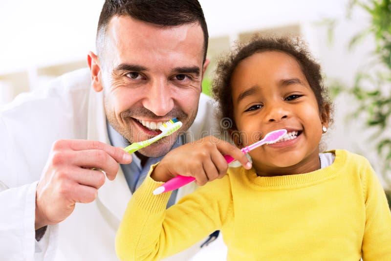 Il pediatra impara il dente di spazzolatura della ragazza africana sveglia immagine stock libera da diritti