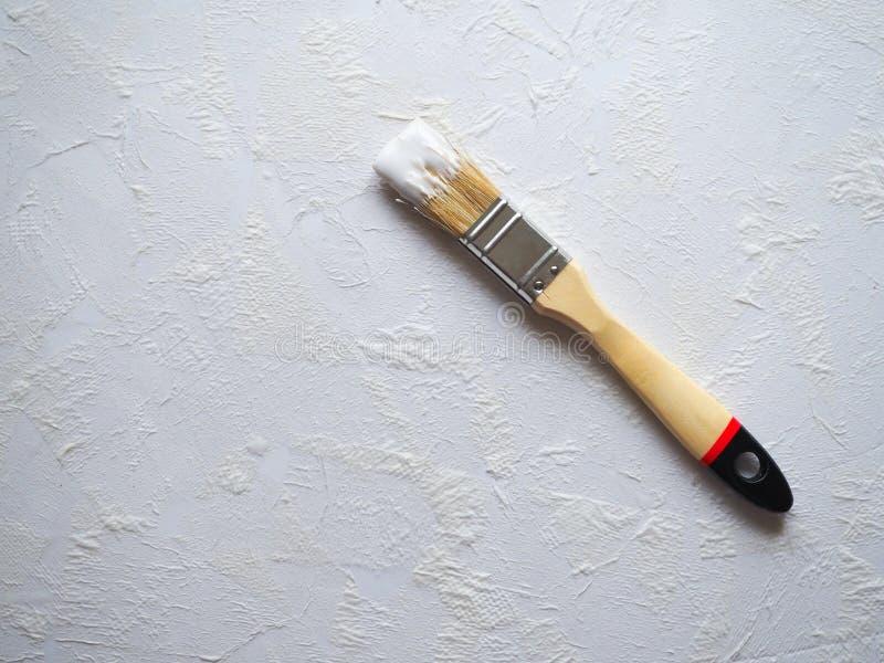 Il pennello con pittura su un bianco ha intonacato la superficie Il concetto della riparazione nell'appartamento immagine stock libera da diritti