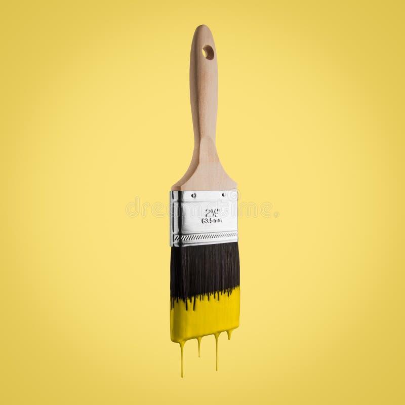 Il pennello ha caricato con colore giallo che gocciola fuori dalla setola fotografia stock