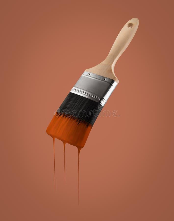 Il pennello ha caricato con colore marrone che gocciola fuori dalle setole immagine stock libera da diritti