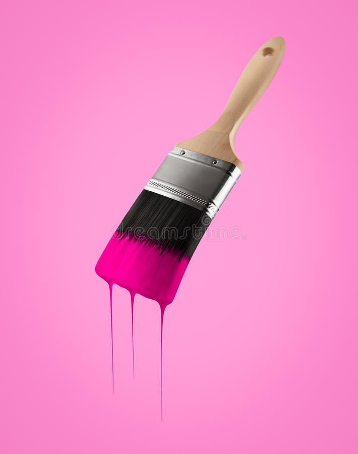 Il pennello ha caricato con colore rosa che gocciola fuori dalle setole immagine stock libera da diritti