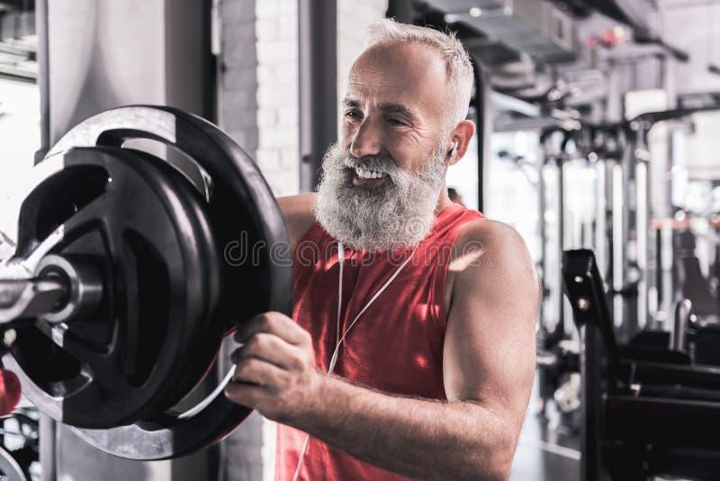 Il pensionato alla moda allegro sta godendo dell'allenamento nel centro atletico immagini stock