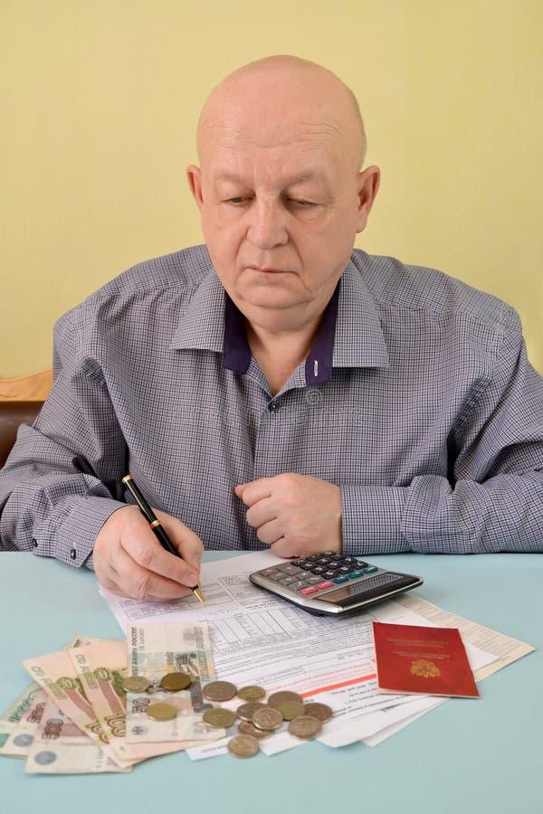 Il pensionato conta le spese di contanti per i pagamenti pratici fotografia stock libera da diritti