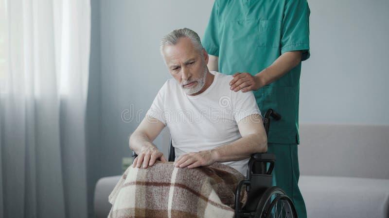 Il pensionato paralizzato in sedia a rotelle non mostra la reazione all'impiegato di cura della casa immagine stock