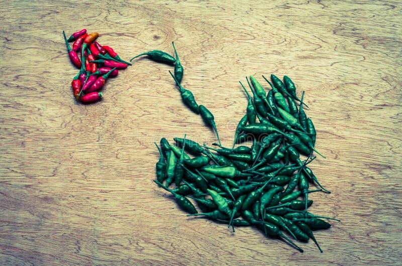 Il pepe tailandese ha sistemato in una forma del cuore nel retro stile immagini stock