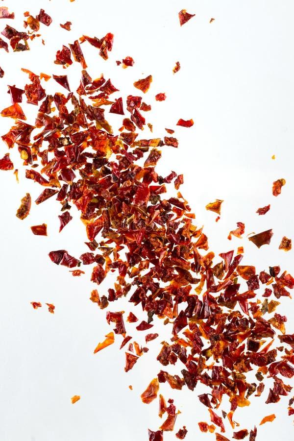 Il peperone secco schiacciato mucchio si sfalda, su fondo bianco, vista superiore, immagine stock