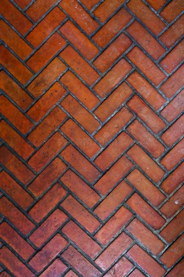 Il percorso pavimentato con il mattone rosso nel modello di zigzag, modello di pietra rosso di stile della spina di pesce del pas fotografia stock libera da diritti