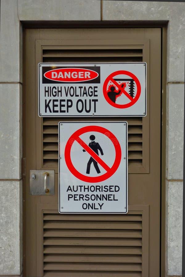 Il pericolo, alta tensione, tiene il segnale di pericolo fuori immagini stock libere da diritti