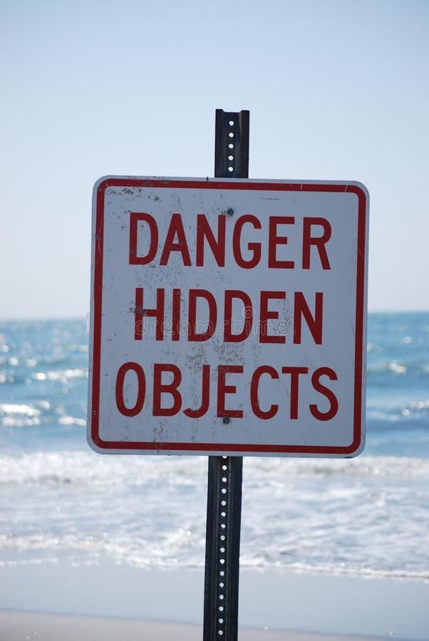 Il pericolo nascosto obietta il segno sulla spiaggia fotografia stock libera da diritti