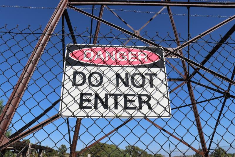 Il pericolo rosso e in bianco e nero, non entra su un recinto di filo metallico fotografia stock libera da diritti