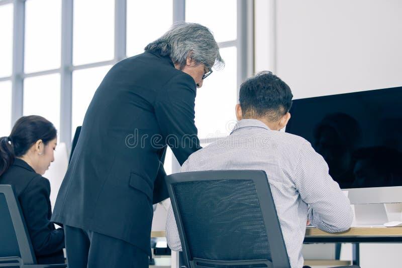 Il personale con anzianità di servizio in vestito sta ordinando un impiegato dell'uomo di osservare un comput immagini stock libere da diritti