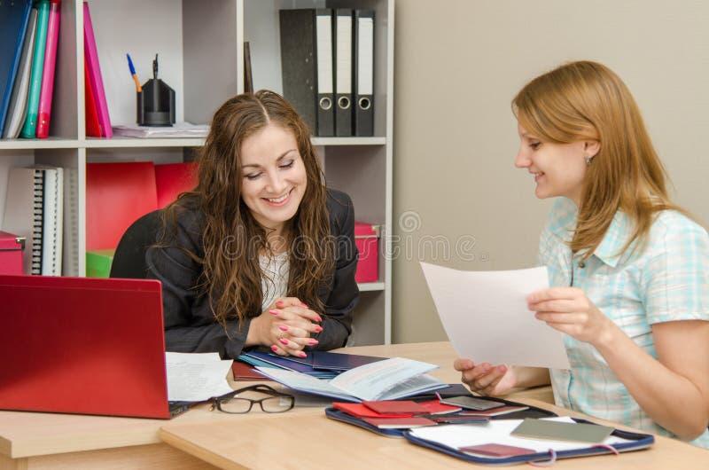 Il personale dello specialista e della ragazza conduce una riuscita intervista immagini stock