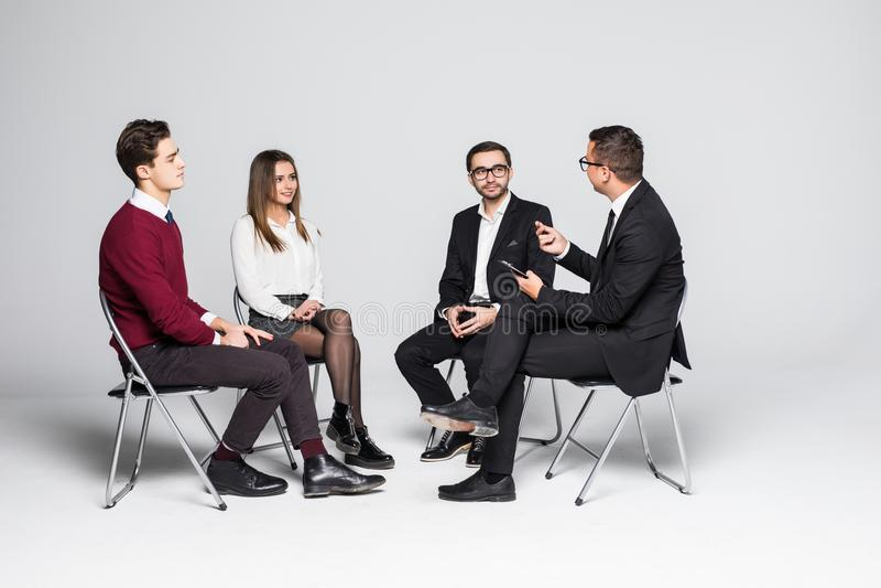 Il personale di ufficio multiculturale che si siede avendo riunione insieme e discute Fasi di vita del gruppo fotografia stock libera da diritti