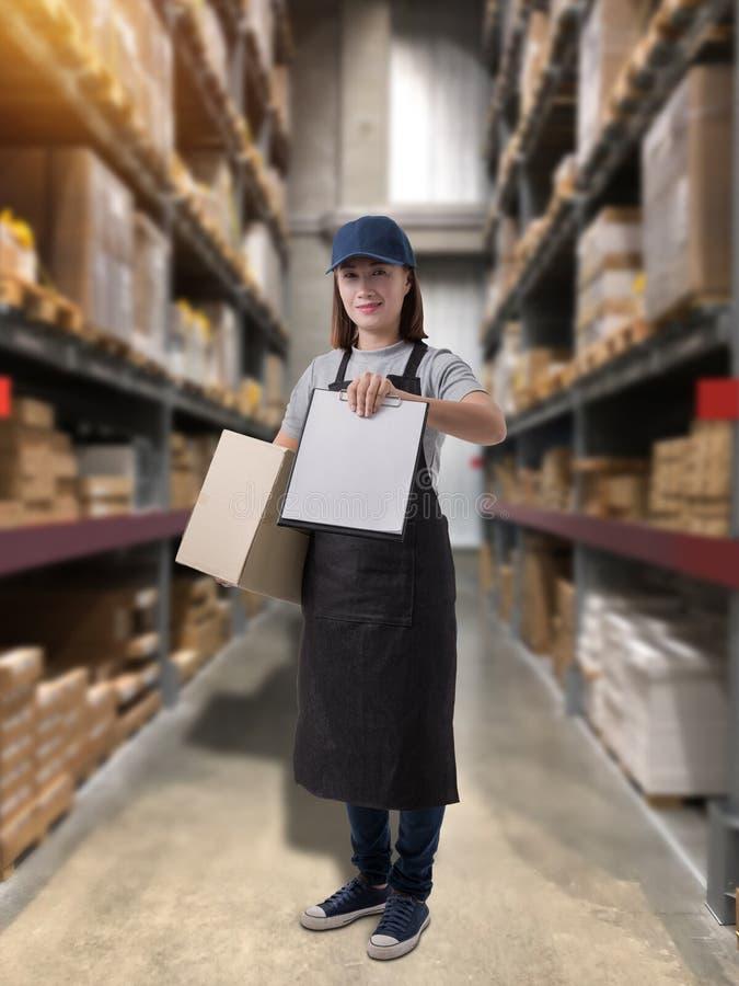 Il personale femminile che consegna i prodotti firma la firma sulla forma della ricevuta del prodotto con le scatole del pacchett immagini stock libere da diritti