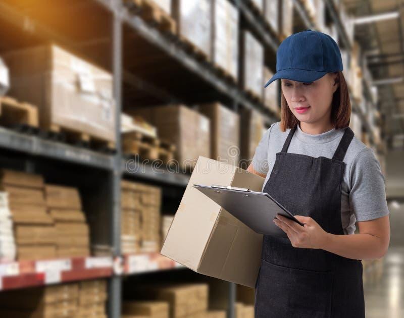 Il personale femminile che consegna i prodotti firma la firma sulla forma della ricevuta del prodotto con le scatole del pacchett immagini stock