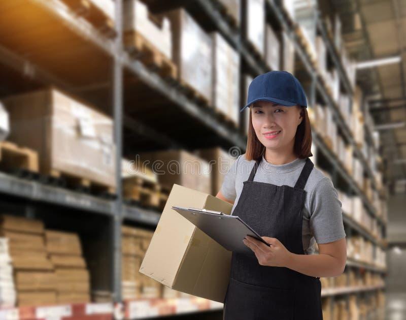 Il personale femminile che consegna i prodotti firma la firma sulla forma della ricevuta del prodotto con le scatole del pacchett fotografie stock