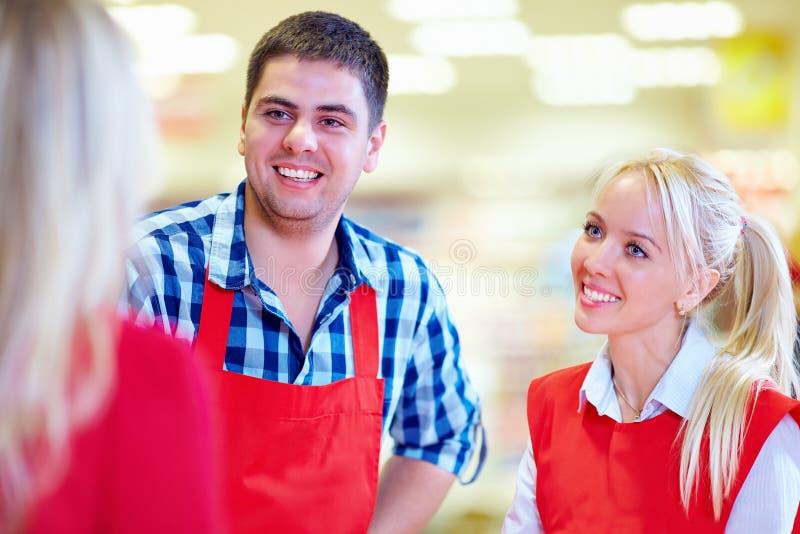 Il personale gentile del supermercato serve il cliente fotografie stock