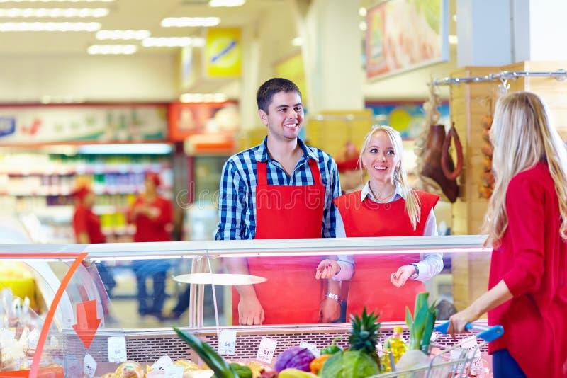 Il personale gentile della drogheria serve il cliente nel centro commerciale immagine stock
