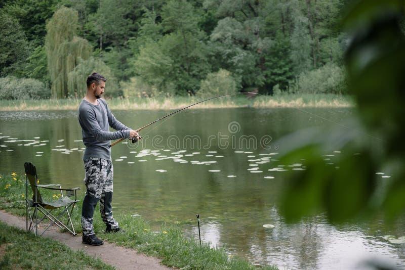 Il pescatore ha fuso la canna da pesca in acqua di fiume o del lago Uomo con l'attrezzatura di filatura nello stile di vita sano  immagini stock