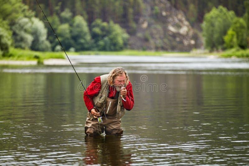 Il pescatore pesca la pesca con la mosca immagini stock libere da diritti