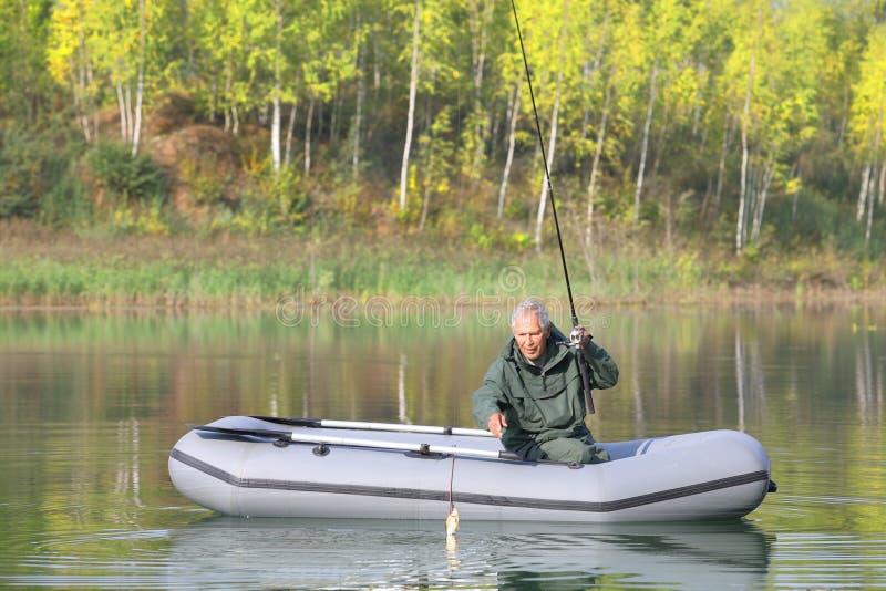 Il pescatore senior ha preso appena una carpa immagine stock
