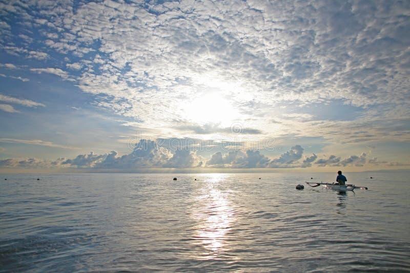 Il pescatore solo assorbe gli squali balena con alimento nelle Filippine immagini stock