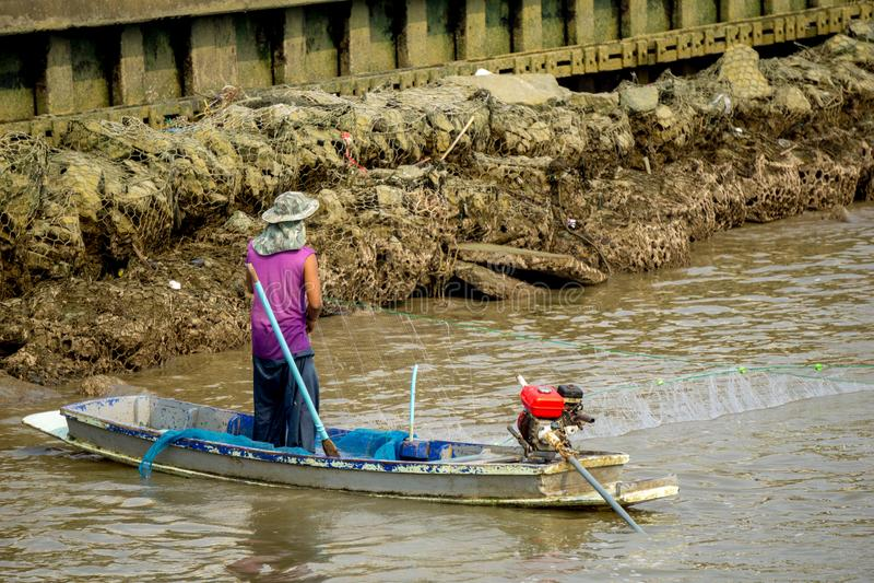 Il pescatore sta pescando dalla rete sulla barca tradizionale tailandese modificata nel fiume fotografia stock libera da diritti