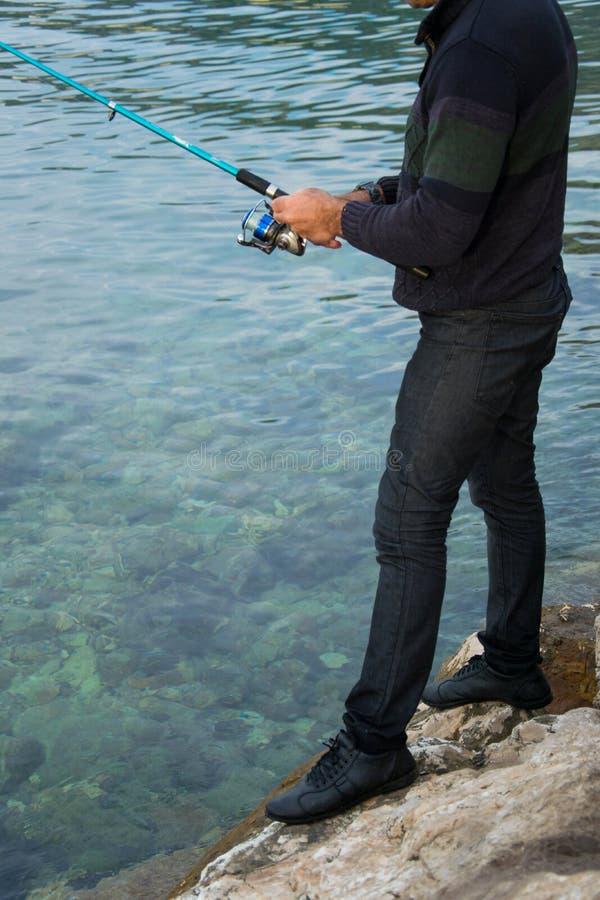 Il pescatore tiene una barretta di pesca con l'amo, attività all'aperto di sport immagini stock libere da diritti