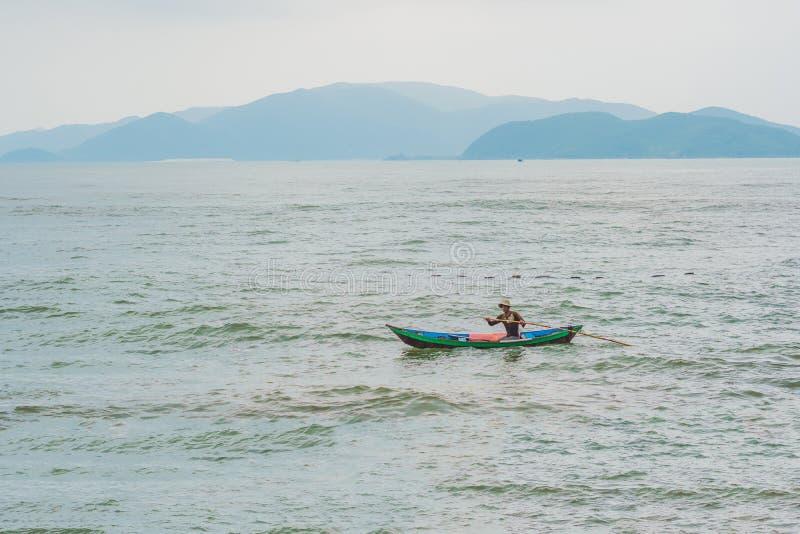 Il pescatore vietnamita nuota in una barca sopra il mare infuriantesi fotografie stock libere da diritti
