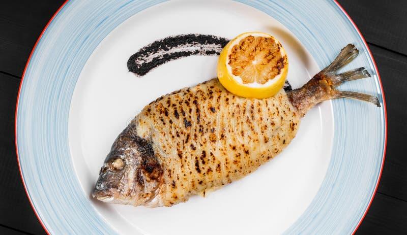 Il pesce arrostito di dorado con il limone ed il tartufo sauce sul piatto su fondo di legno Piatto delizioso di frutti di mare immagine stock libera da diritti