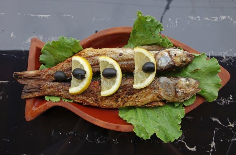 Il pesce della muggine grigliato con il limone e le olive è servito sulle terraglie dell'argilla fotografie stock libere da diritti