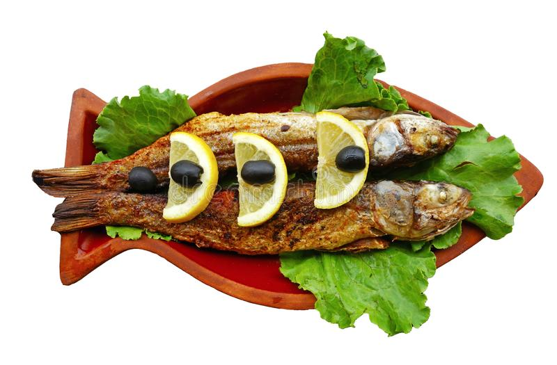 Il pesce della muggine grigliato con il limone e le olive è servito sulle terraglie dell'argilla fotografia stock libera da diritti
