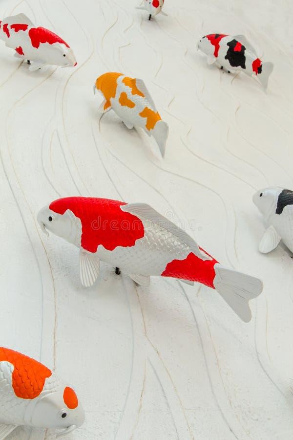 Il pesce delle carpe o la statua del pesce di koi sulla parete del cemento per decorare, stucco handcraft del pesce della carpa a immagine stock