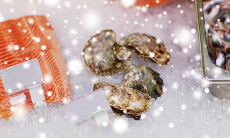 Il pesce e le ostriche di color salmone su ghiaccio alla drogheria si bloccano fotografia stock