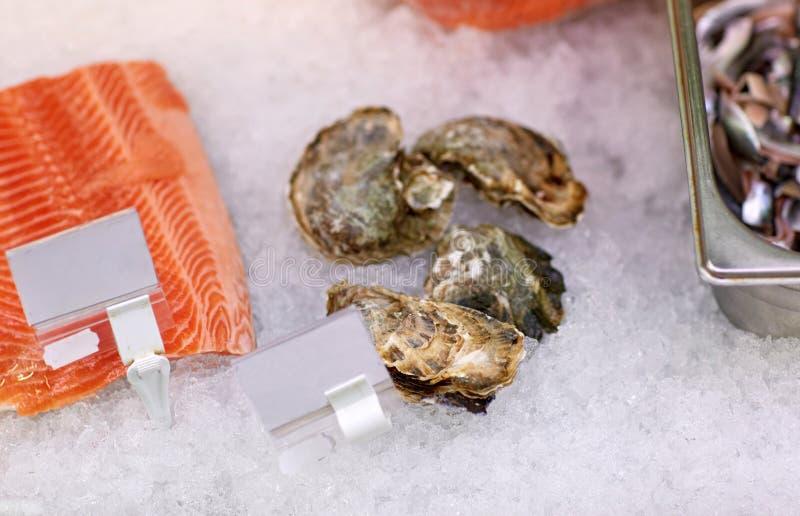 Il pesce e le ostriche di color salmone su ghiaccio alla drogheria si bloccano immagini stock