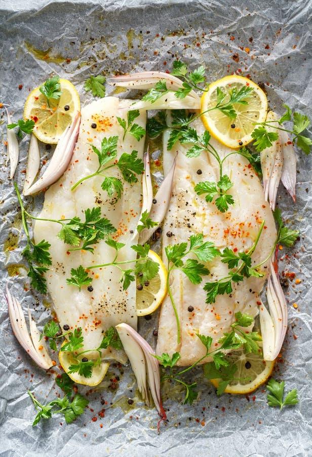 Il pesce fresco, i filetti di merluzzo con prezzemolo, le fette del limone, la cipolla e le spezie hanno preparato per cuocere su immagine stock libera da diritti