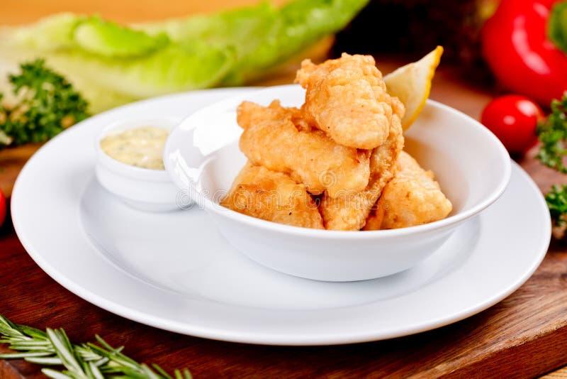 Il pesce fritto nel grasso bollente croccante è servito con salsa sul piatto bianco fotografie stock