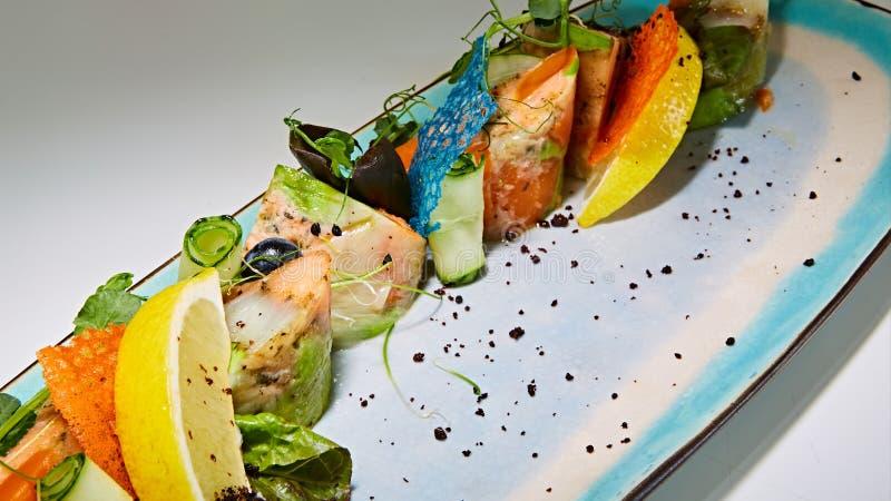 Il pesce fritto rotola con le erbe e le verdure sul piatto blu fotografia stock
