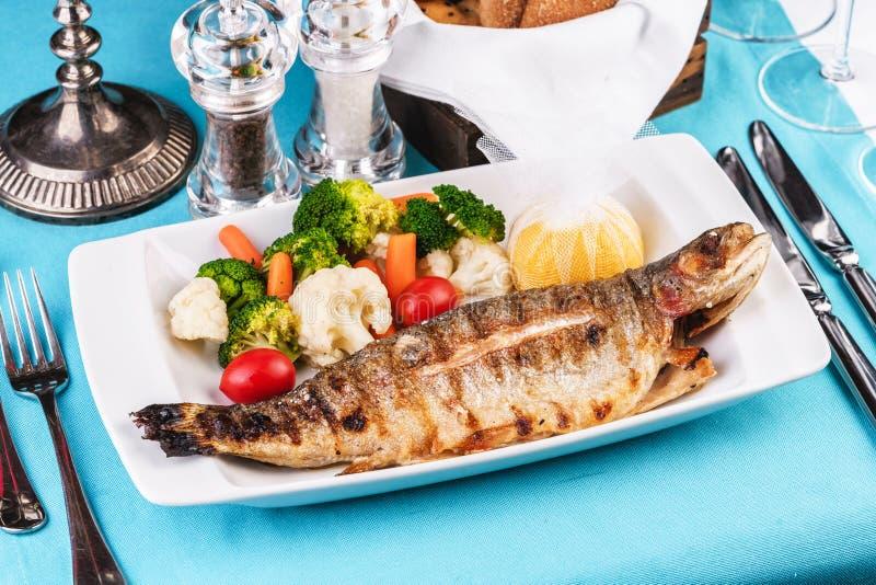 il pesce intero cotto nel forno, è servito con un'insalata delle verdure, dei verdi, della rucola, degli anelli di cipolla, del p immagine stock