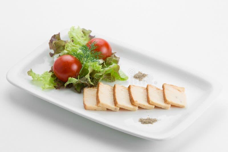 Il pesce oleoso ha fumato con la lattuga ed i pomodori dell'insalata mista su bianco fotografia stock