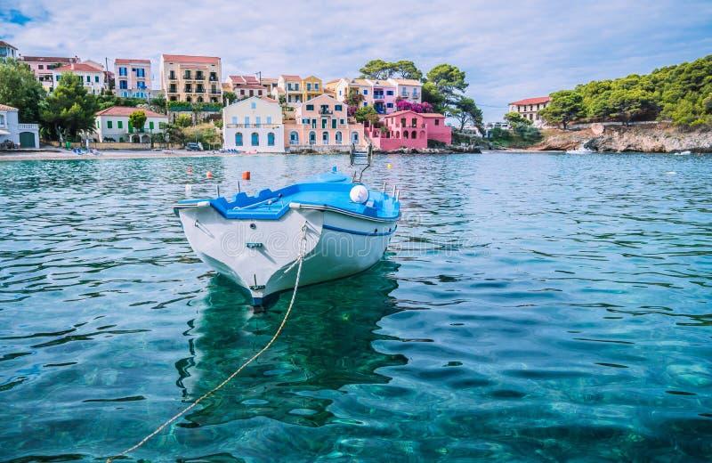 Il peschereccio bianco nel blu ha increspato la baia dell'acqua di mare nel villaggio di Asso, l'isola di Kefalonia, Grecia immagini stock