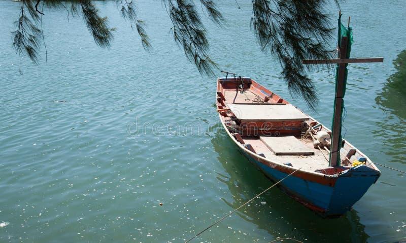 Il peschereccio del pescatore si è ancorato al pilastro sotto il pino con il fondo verde blu naturale dell'acqua di mare nave mar fotografia stock libera da diritti