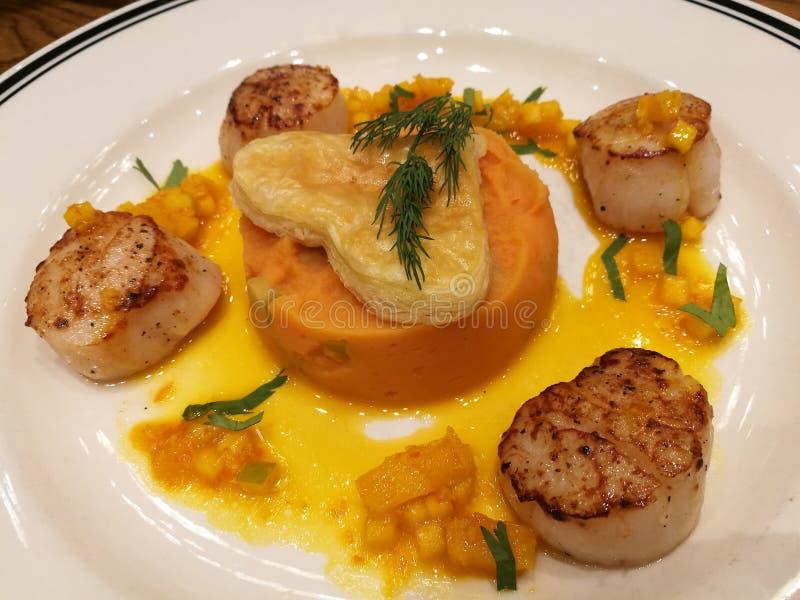 Il pettine scottato fritto dell'Hokkaido è servito con la patata dolce schiacciata cremosa e la cima arancio della salsa con la t immagine stock