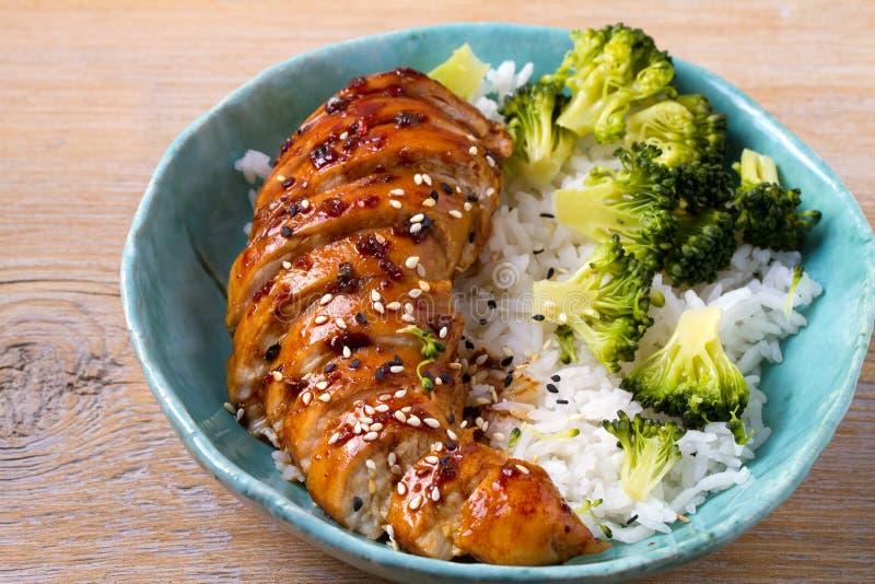 Il petto di pollo in aceto balsamico e lo zucchero bruno sauce spruzzato con i semi di sesamo Pollo con riso e broccoli immagine stock