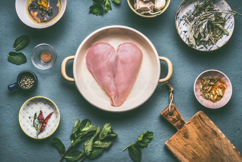 Il petto di pollo nella forma del cuore in vaso con la cottura degli ingredienti lancia su fondo grigio, vista superiore fotografia stock