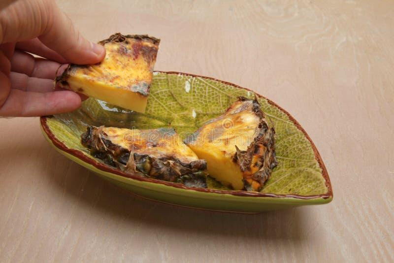 Il pezzo decomposto di ananas ha tenuto in una mano fotografie stock